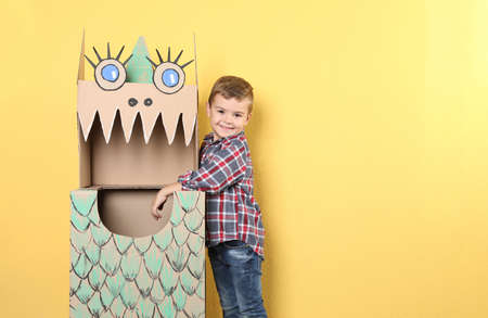 Cute little boy playing with cardboard dragon on color background. Space for text