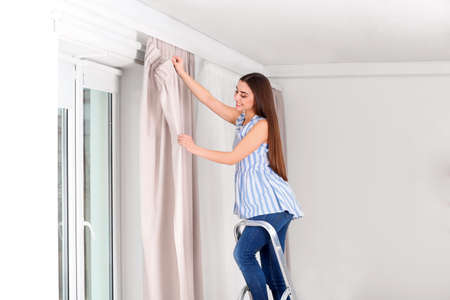 Young pretty woman hanging window curtain in room
