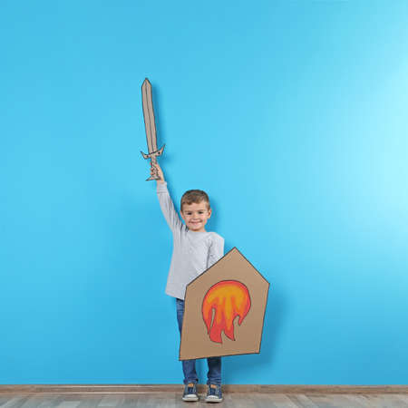 Cute little boy playing with cardboard sword and shield near color wall. Space for text