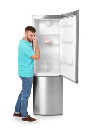 Young man near refrigerator with expired sausage on white background Фото со стока
