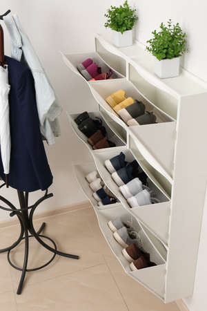 Shoe cabinet with footwear in room. Storage ideas Stockfoto