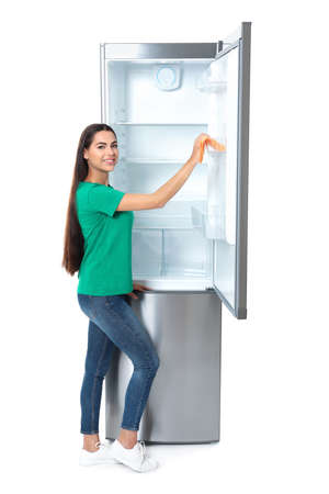Young woman cleaning refrigerator with rag on white background