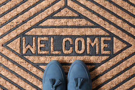 Blue female shoes on brown welcome doormat, top view