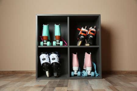 Pairs of roller skates on shelves near light wall