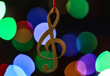 Wooden treble clef against blurred lights. Christmas music