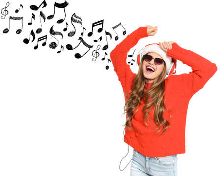 Young woman in Santa hat with headphones and music notes against white background, space for text. Christmas and New Year celebration Stock Photo