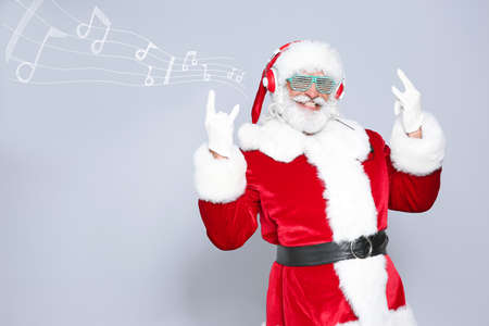 Santa Claus with headphones, party glasses and music notes on light background, space for text. Christmas and New Year celebration