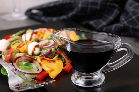 Gravy boat of balsamic vinegar on plate with vegetable salad, closeup