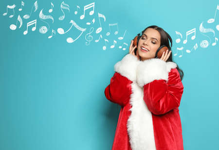 Young woman in Santa coat with headphones and music notes against blue background, space for text. Christmas and New Year celebration Stock Photo