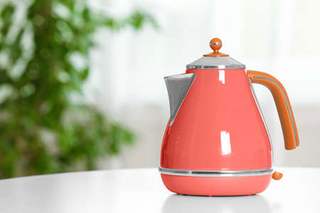 Stylish electrical kettle on table in room, space for text. Design with living coral color