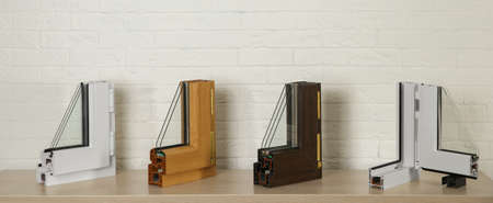 Samples of modern window profiles on table against brick wall. Installation service