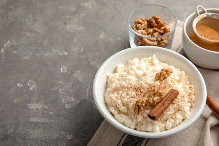 Creamy rice pudding with cinnamon and walnuts in bowl served on grey table. Space for text