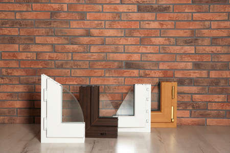 Samples of modern window profiles on floor against brick wall. Installation service