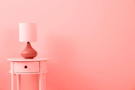 Stijlvolle lamp op tafel tegen kleurmuur, ruimte voor tekst. Ontwerp met levende koraalkleur Stockfoto