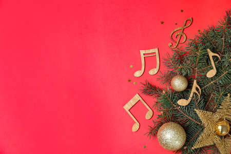Platliggende compositie met dennenboom, kerstdecor en houten muzieknoten op een achtergrond in kleur. Ruimte voor tekst