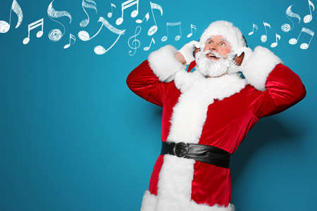 Santa Claus with headphones and music notes on blue background, space for text. Christmas and New Year celebration