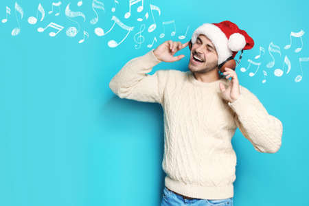 Young man in Santa hat with headphones and music notes against blue background, space for text. Christmas and New Year celebration Stock Photo