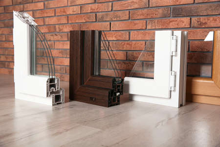 Samples of modern window profiles on floor against brick wall. Installation service