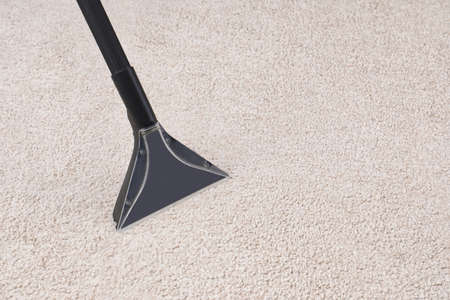 Removing dirt from carpet with vacuum cleaner indoors, closeup. Space for text 版權商用圖片