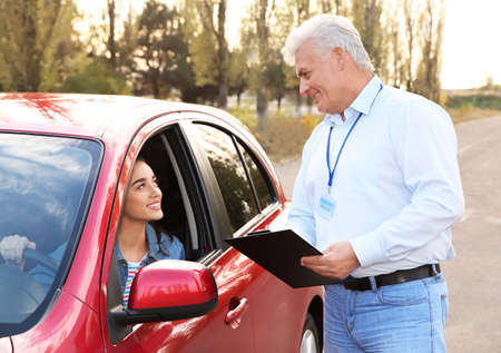 Instructor near woman in car, outdoors. Passing driving license exam Banque d'images