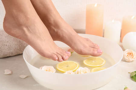 Woman putting her feet into bowl with water, roses and lemon slices on floor, closeup. Spa treatment Фото со стока