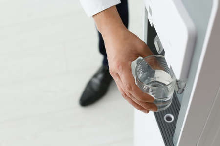 Man vullen glas van waterkoeler op lichte achtergrond, close-up. Ruimte voor tekst Stockfoto