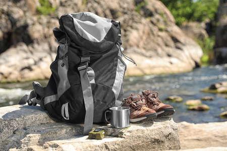 Traveling gear on rock near river. Summer camp