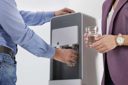 Employees taking glasses of water from cooler in office, closeup
