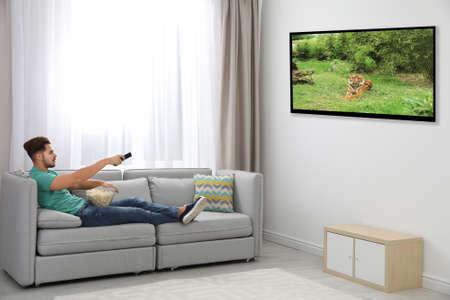 Young man watching TV and eating popcorn on sofa at home 版權商用圖片