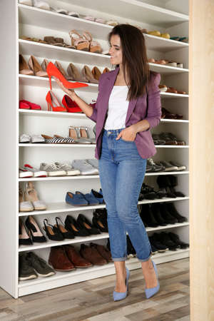 Young woman choosing shoes in dressing room. Idea for interior design