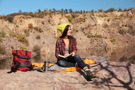 Female camper reading book while sitting on sleeping bag in wilderness
