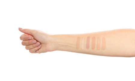 Woman testing different shades of liquid foundation on her hand against white background, closeup Stock Photo