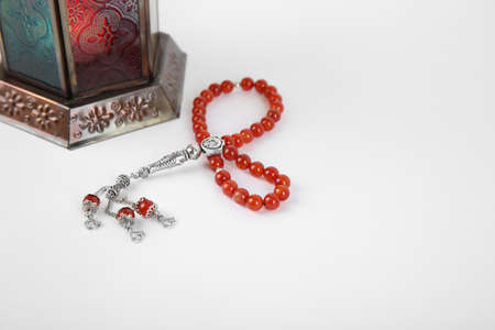 Muslim lamp and prayer beads on white background. Space for text Imagens