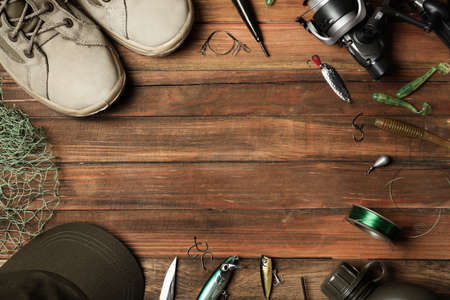 Flat lay composition with fishing equipment and space for text on wooden background Foto de archivo