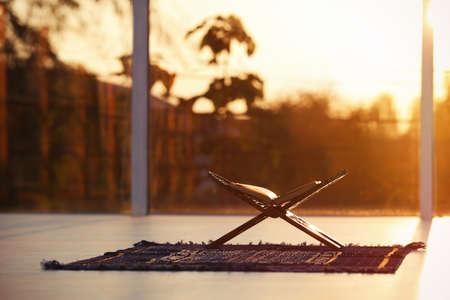 与在穆斯林祷告席子的开放古兰经的Rehal在室内。文本的空间