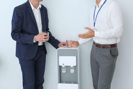 Men having break near water cooler on white background, closeup
