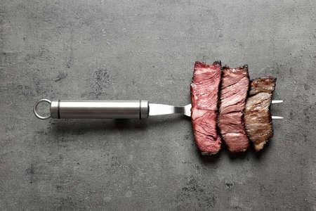 Forchetta con pezzi di deliziosa carne alla brace su sfondo grigio, vista dall'alto