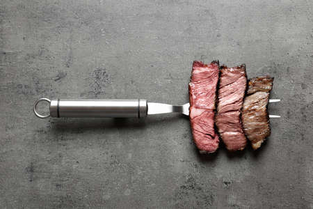 Fork with pieces of delicious barbecued meat on gray background, top view Standard-Bild