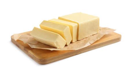 Tabla de madera con bloque cortado de mantequilla sobre fondo blanco.