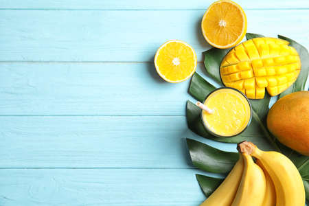 Glass of fresh mango drink and tropical fruits on color wooden background, top view. Space for text