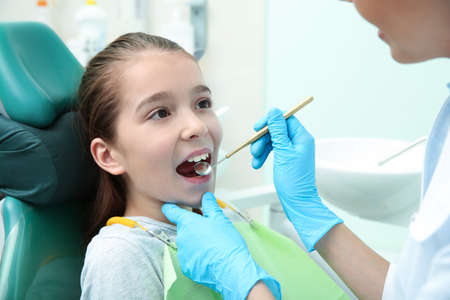 Professional dentist working with little patient in modern clinic
