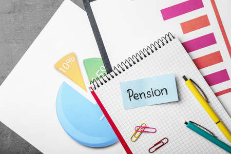 Paper with word Pension, stationery, notebook and charts on table, top view