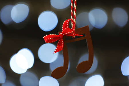 Wooden music notes against blurred Christmas lights