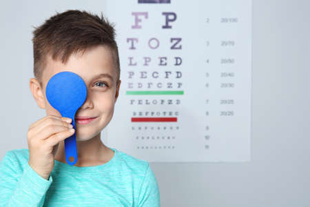 Cute little boy visiting children's doctor, space for text. Eye examination Stockfoto
