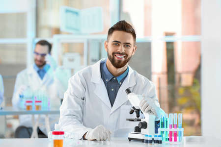 Young scientist with microscope in laboratory. Chemical analysis