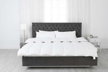 Large comfortable bed in light room. Stylish interior Archivio Fotografico