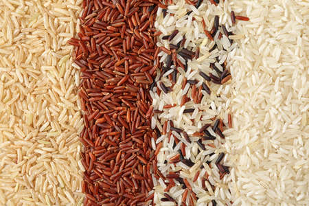 Brown and other types of rice as background, closeup