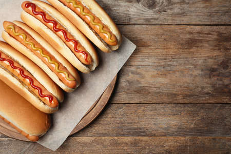 Tasty fresh hot dogs on wooden table, top view. Space for text
