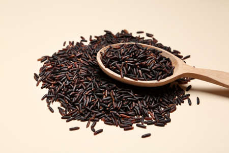 Black rice and wooden spoon on color background
