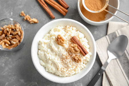 Creamy rice pudding with cinnamon and walnuts in bowl served on grey table, top view Stock Photo